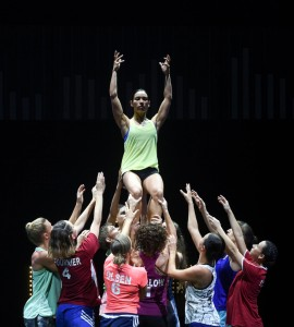 Champions, Marnie Palomares in the green top, held by the ensemble, photo © Heidrun Lohr